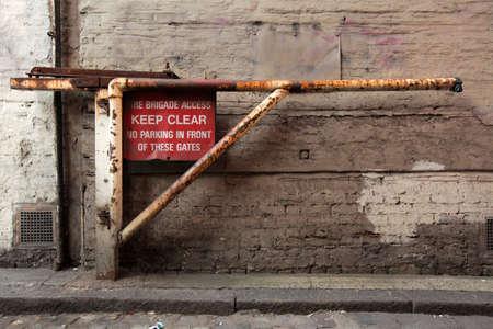 Oude verroeste slagboom met een KEEP CLEAR teken en informatie die deze weg zal worden gebruikt voor evacuatie in noodgevallen, Londen