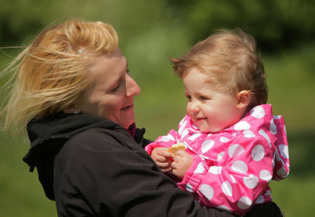 Happy mother holding her daughter in a park on a windy spring day photo