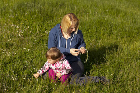 Mother and daughter creating flower wreaths in the park in spring photo