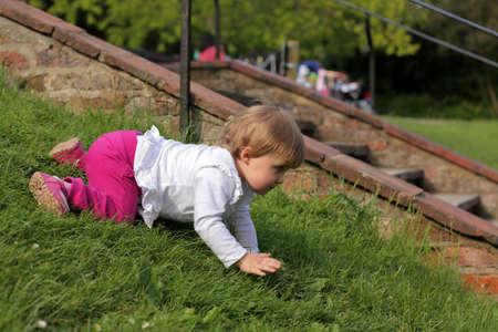 bebe gateando: Beb� lindo que se arrastra por la peque�a colina en el parque