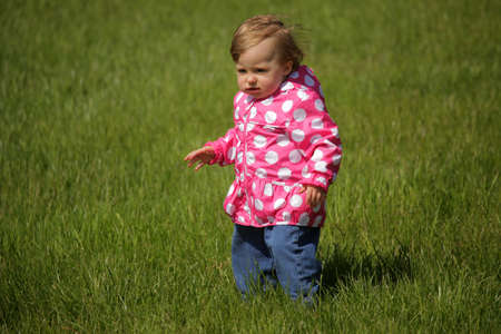 Baby girl standing on the grass in the garden on a windy day in spring photo