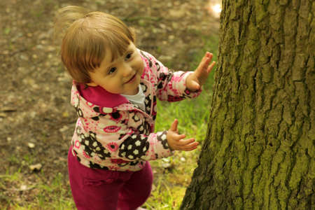 Young little girl hiding behind the tree while playing hide and seek with her mom photo
