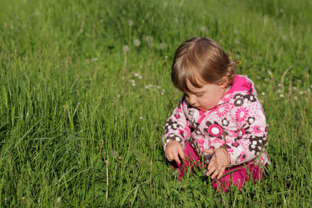 Baby girl sitting in the grass in the forest in spring photo