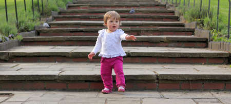 Cute baby girl walking down the wide stairs in the park photo