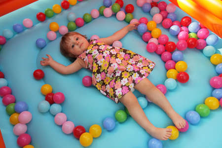 Little girl surrounded by colourful balls on the floor in a bouncy castle photo