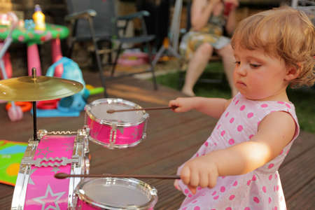 yard stick: Cute little girl playing toy drums in the home garden