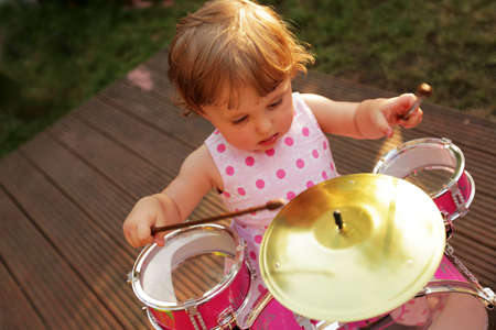 Cute little girl playing toy drums in the home garden photo