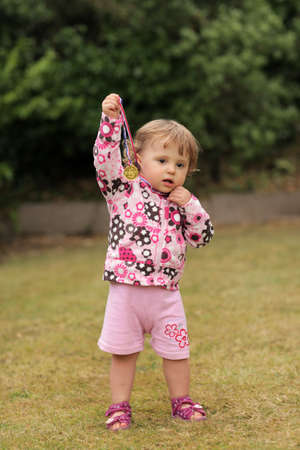Portrait of a cute little baby girl proudly showing her first gold medal won in the nursery running competition photo