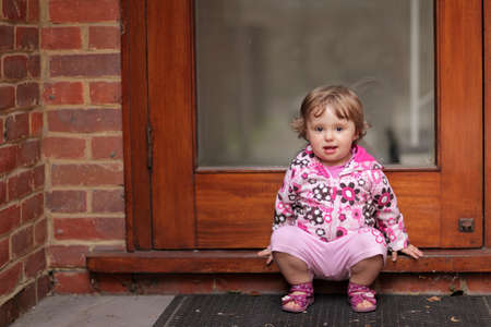 Cute little baby girl waiting for her mum at the doorstep of their home photo