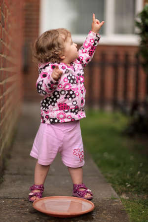Little girl pointing her finger up towards the bird she has just seen photo