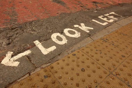 Look left white sign at a pedestrian crossing in London, UK photo