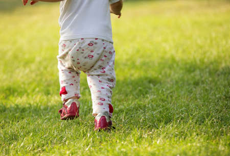 Baby girl running in the park on a sunny spring afternoon photo