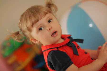 Portrait of a cute little baby girl with big inflatable beach ball in the background photo