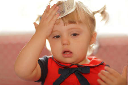 worrying: Little baby girl holding 20 pounds banknote with worrying look Stock Photo