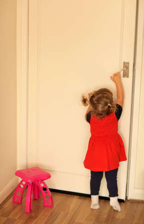객실 문을 열려고하는 귀여운 아기 소녀