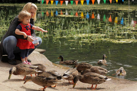 Mother and daughter feeding ducks by the lake on a family day out