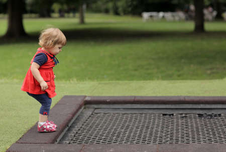 effortless: Little girl preparing to jump on a trampoline in the park Stock Photo