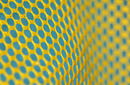 Texture of a plastic yellow net over blue background photo