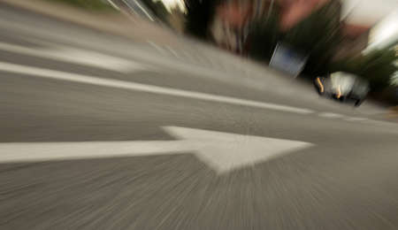 one lane sign: Blurred dynamic picture of a white straight arrow sign on the street