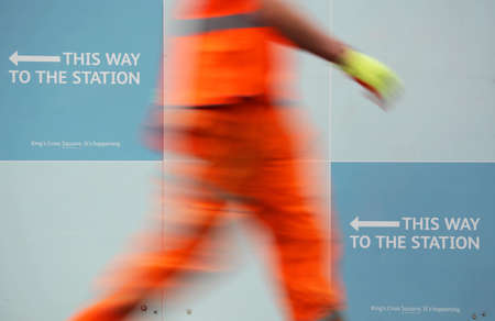 passing the road: Blurred image of a person passing sign showing direction to the train station Stock Photo