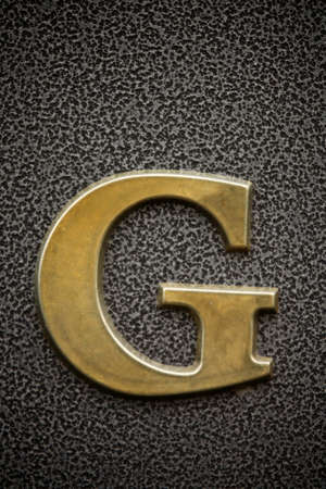 The letter G on the grainy metallic background photo