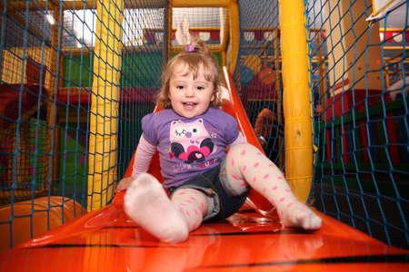 Meisje dat pret op een dia in een overdekte activiteitencentrum Stockfoto