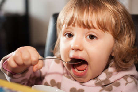 devouring: Portrait of a cute little baby girl eating pasta for dinner