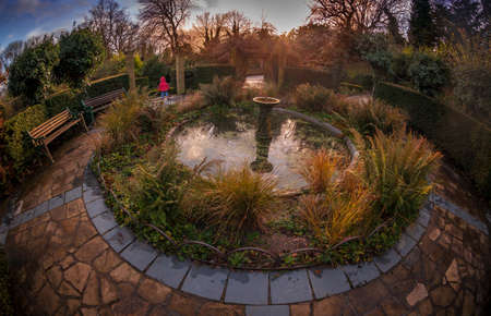 Sunset, fisheye view of a small fountain in the Rookery in Streatham Common Park in London, UK photo