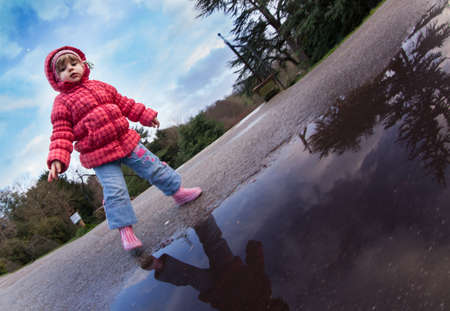 Baby girl standing in front of the puddle after rain in english countryside
