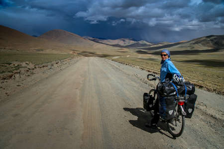 Single female cyclist on the bicycle in the stunning remote part of Western Tibet Stock Photo