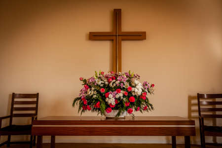 Christian cross, altar, candle and flower bouquet in a church chapel