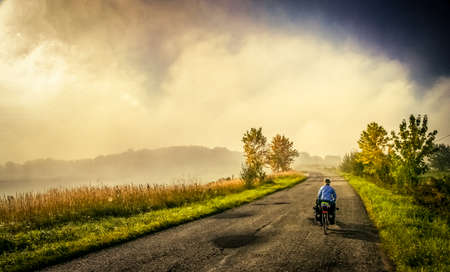 Woman cycling alone on the narrow rural roads in Poland