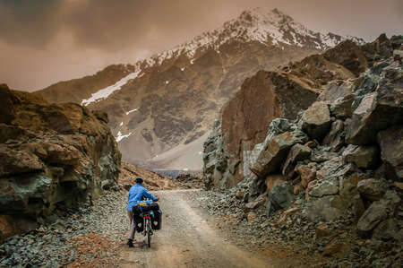 endeavor: Woman cycling on a difficult mountain road towards Shandur Pass in northern Pakistan