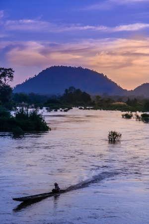 det: Man in a pirogue on a Mekong river, Don Det, Laos