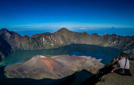 Tourist sitting on the rim of the crater of Gunung Rinjani volcano in Lombok island, Indonesia