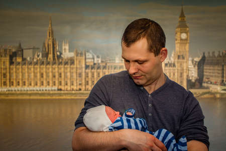 first miracle: Father with his newborn son posing for a photo after birth with the Houses of Parliament and Big Ben clock tower in the background, London, UK