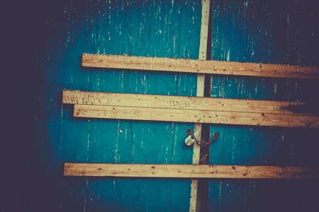 Padlock and nailed planks securing blue gates photo