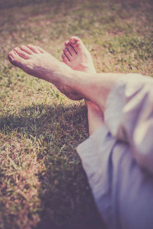 Men s feet on the grass in the park in summer