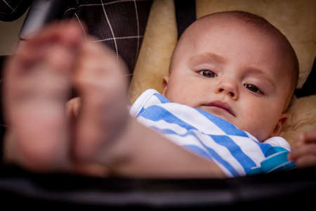 Cute and adorable baby boy relaxing in his pushchair Stock Photo - 30644677