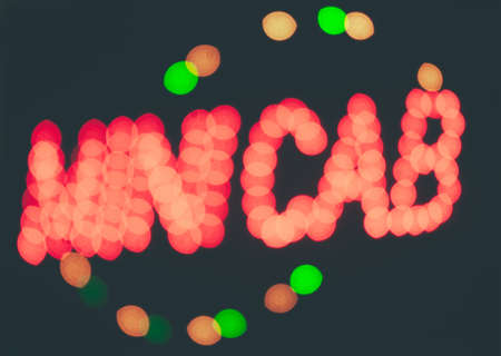 Diffused lights of a neon spelling minicab photo