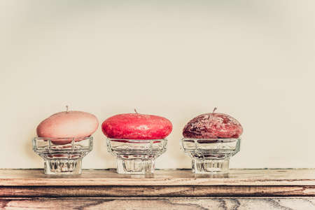 Three candles standing on a wooden panel above fireplace photo