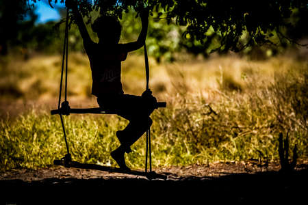 Silhouette of a Malagasy girl having fun on a swing, Madagascar photo