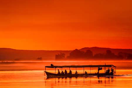 Boat with passengers during beautiful sunset over Tsiribihina river in Madagascar photo