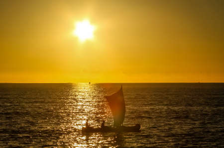 Traditional fishing pirogue sailing on the ocean photo