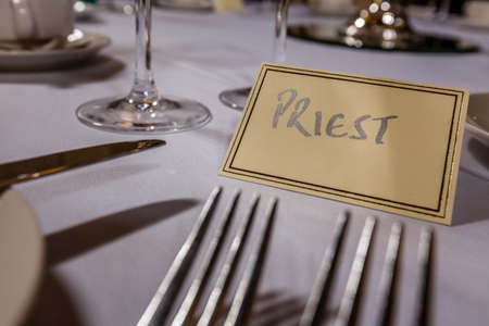 Priest seat at a table at wedding reception photo