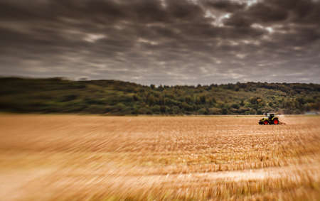Tractor plowing the field in rural part of England photo