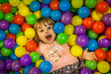 Little girl having fun on an indoor playground in an activity centre photo