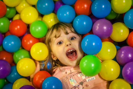 Little girl having fun on an indoor playground in an activity centre Imagens - 33025355
