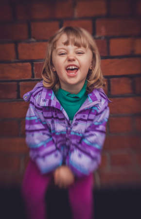 loudly: Cute little girl laughing loudly while playing outside Stock Photo
