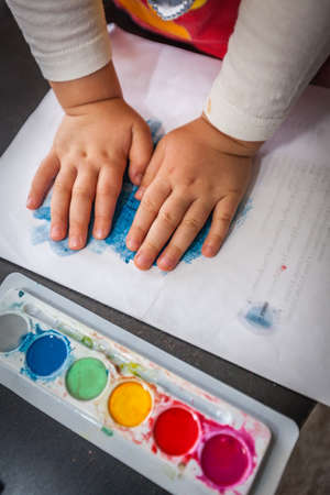 absorbed: Little girl painting watercolors with her hands